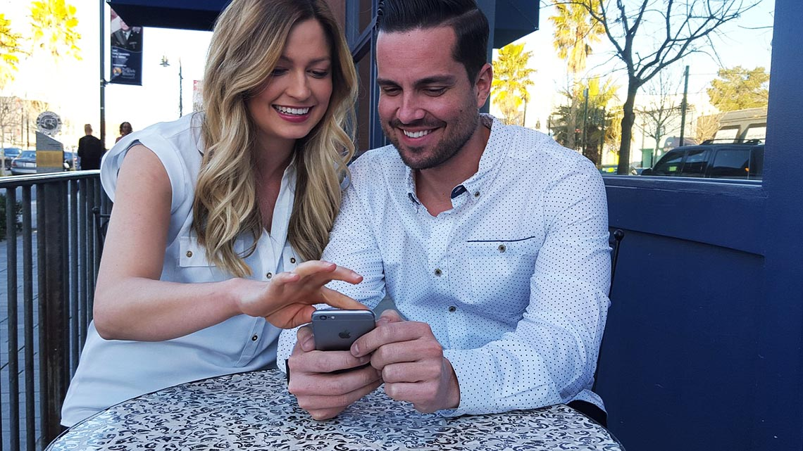 Mann erklärt Frau am Tisch wie das Smartphone funktioniert