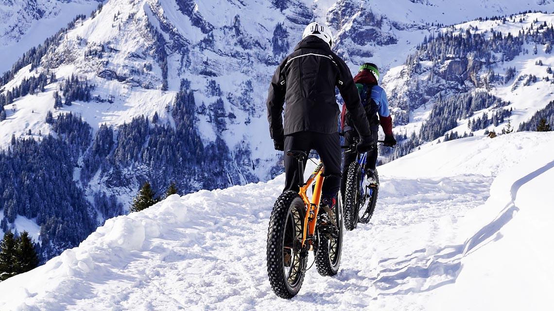 Mann und Frau in den Bergen gemeinsam auf 2 Fahrrädern