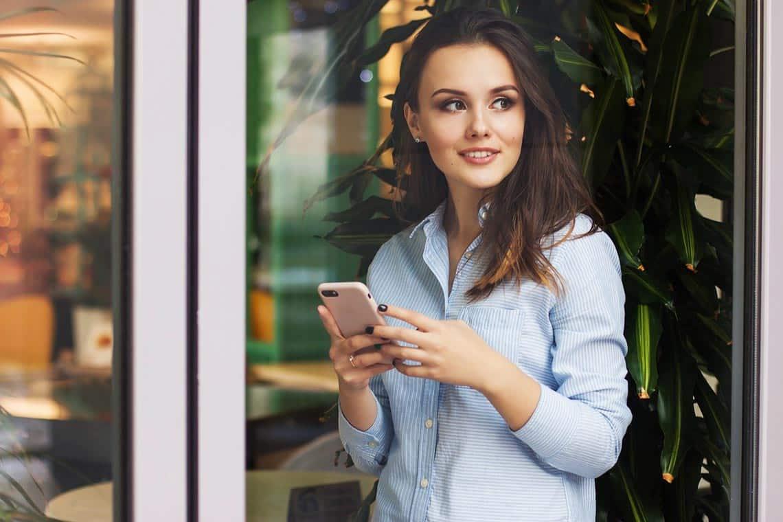 Frau mit Smartphone und denkt darüber nach was Sie schreiben soll