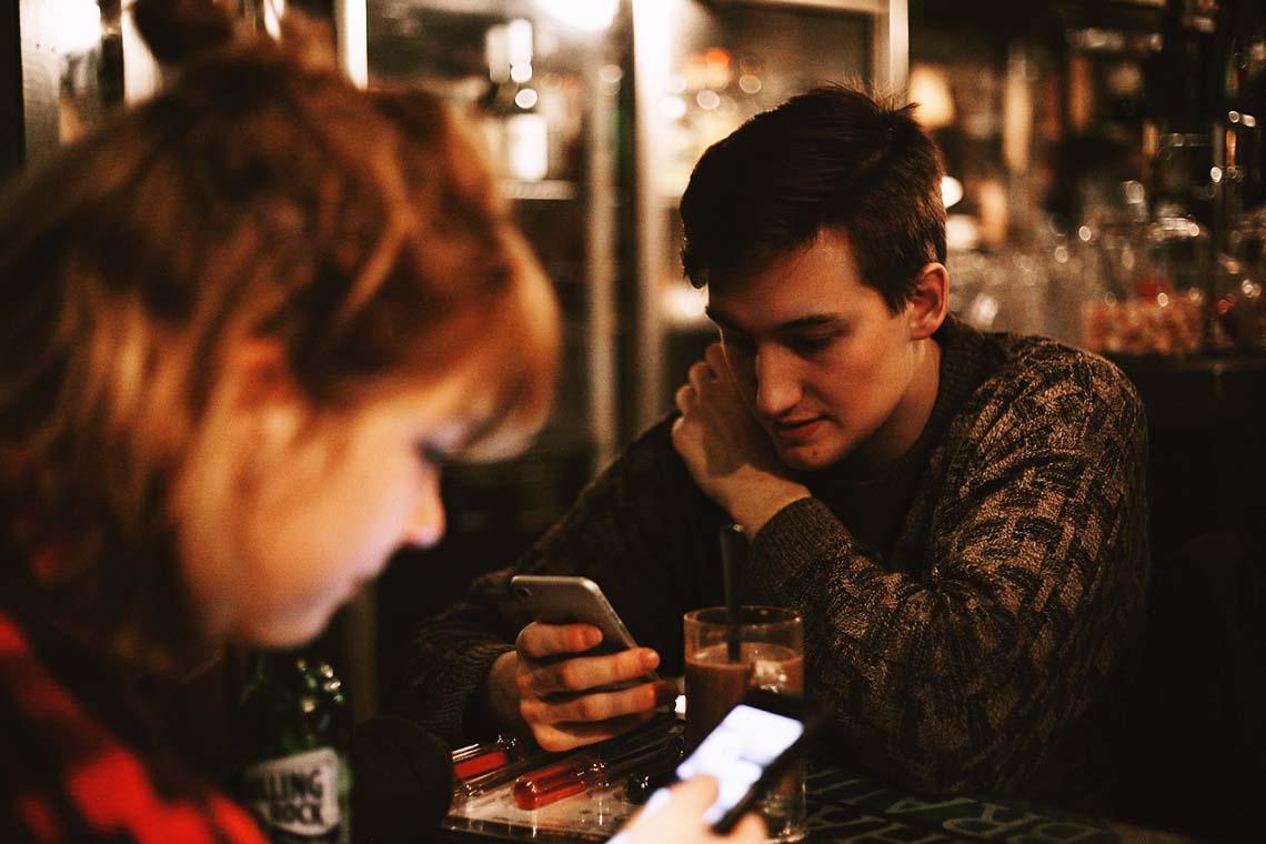Frau und Mann mit Smartphone in einer Bar