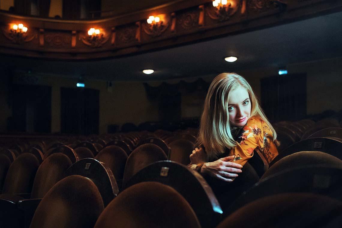 Frau im Kinosaal sitzend