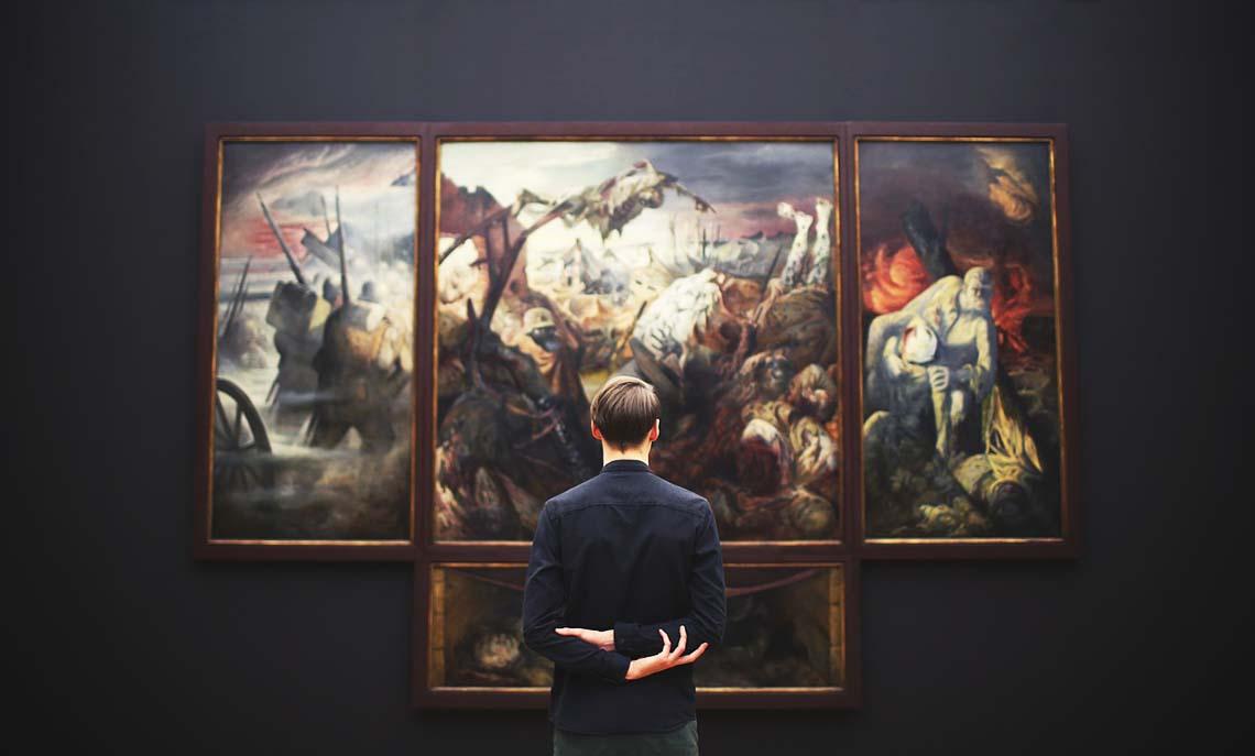 Mann vor Gemälden im Museum