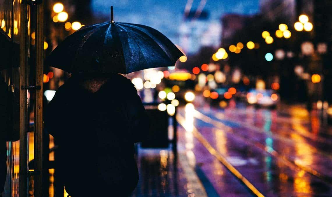 Nachbarschaft - Mann mit Schirm an der Straße