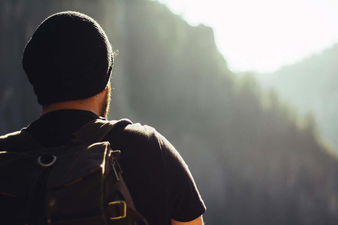 Mann mit Rucksack vor Bergen
