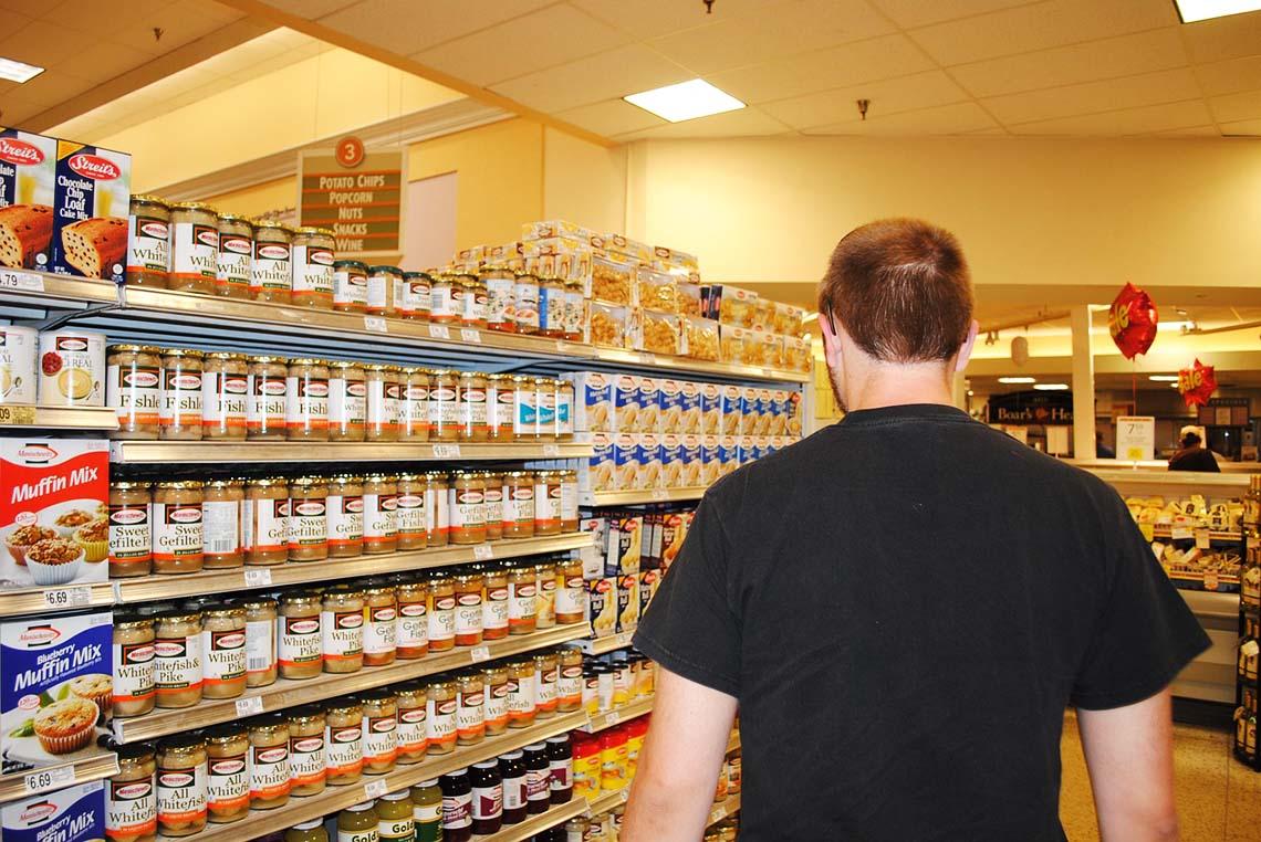 Mann vor einem Supermarkt-Regal