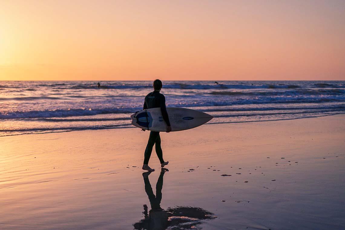Mann mit Surfbrett am Strand im Urlaub