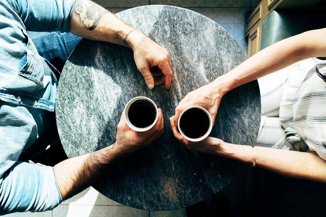 Frau und Mann mit Café am Tisch