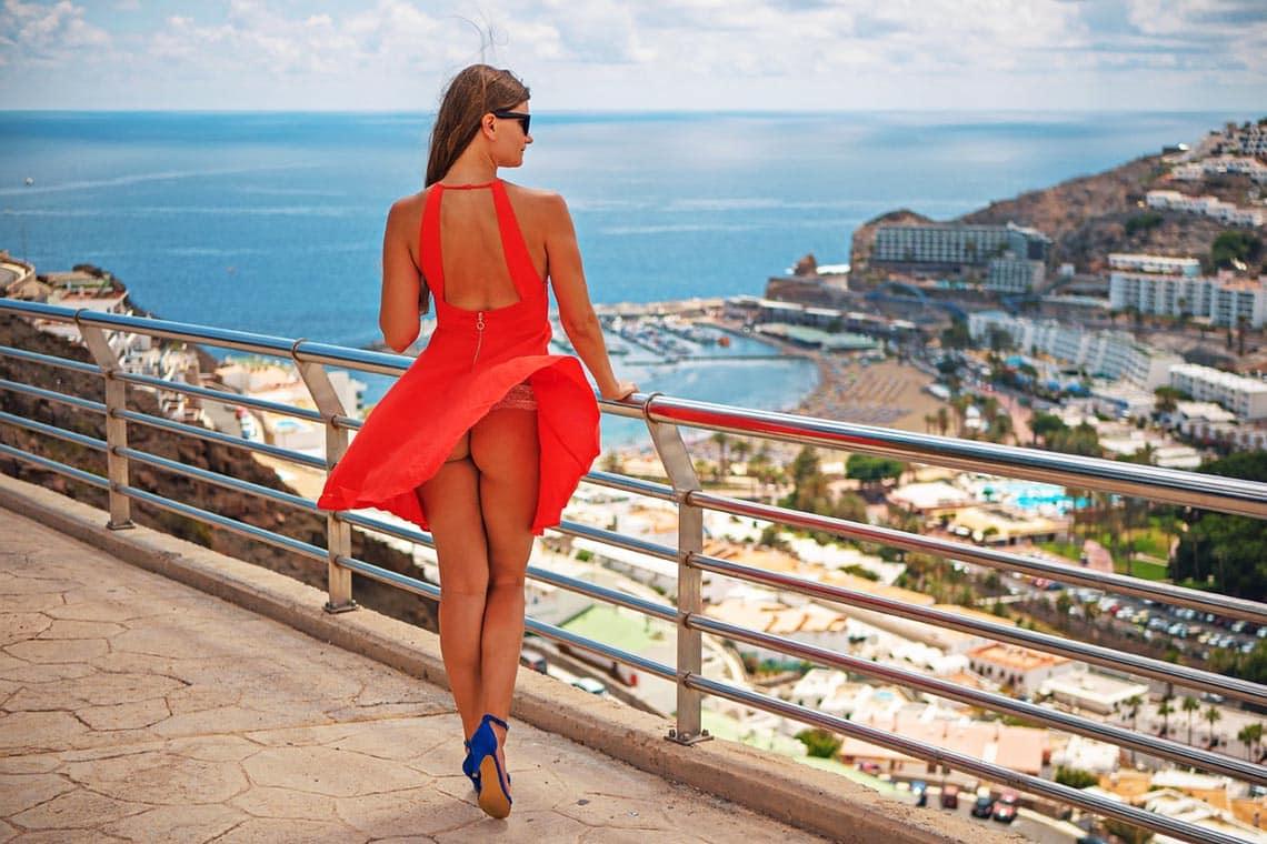 rotes Kleid einer Frau wird vom Wind erfasst