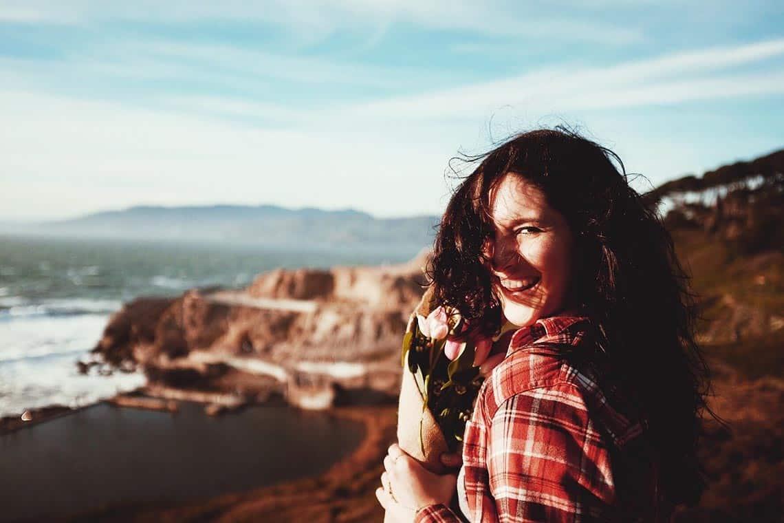 Frau blickt in die Kamera an einer Steilküste und lacht