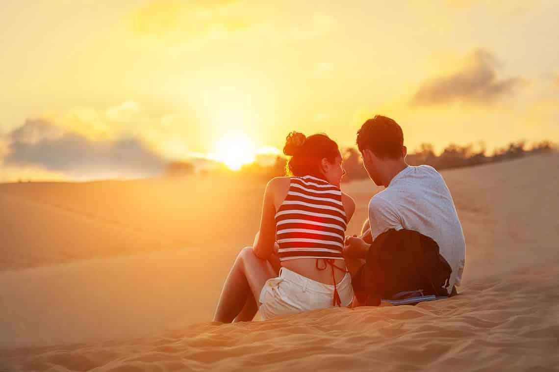 Frau mit Mann am Strand und interessiert sich für das was er erzählt