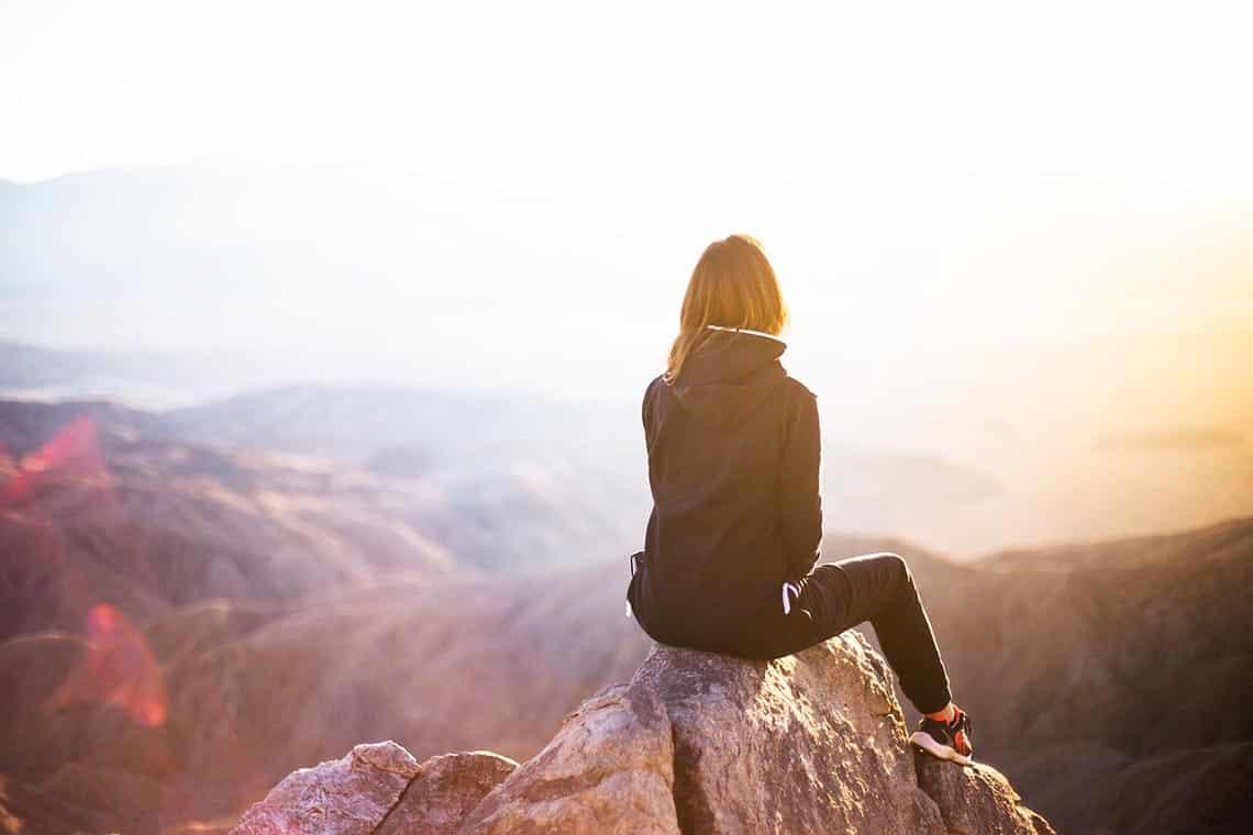 Frau sitzt auf einem Felsvorsprung auf einem Berg