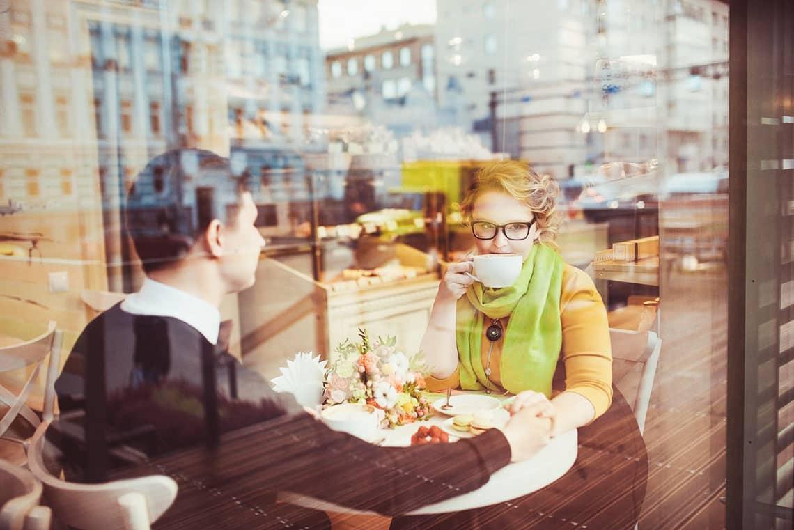 Mann und Frau sitzen im Cafe und Frau hört ihm beim Trinken zu