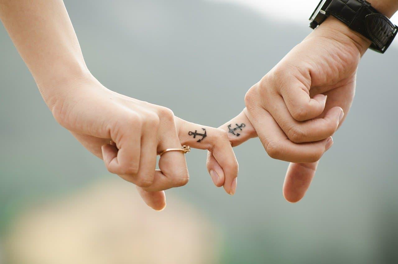 Zwei Menschen halten sich an den Fingern